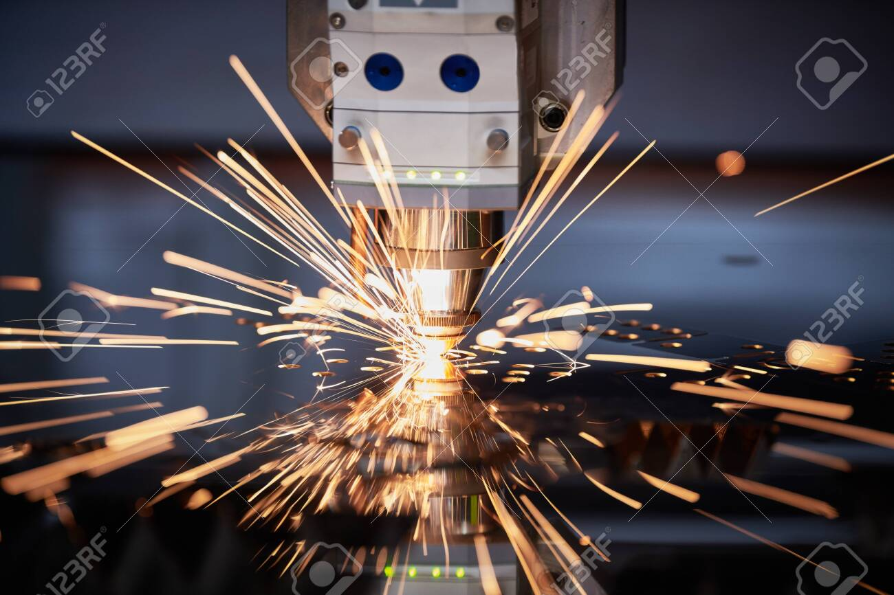 Laser cutting. Metal machining with sparks on CNC laser engraving maching - 125520670
