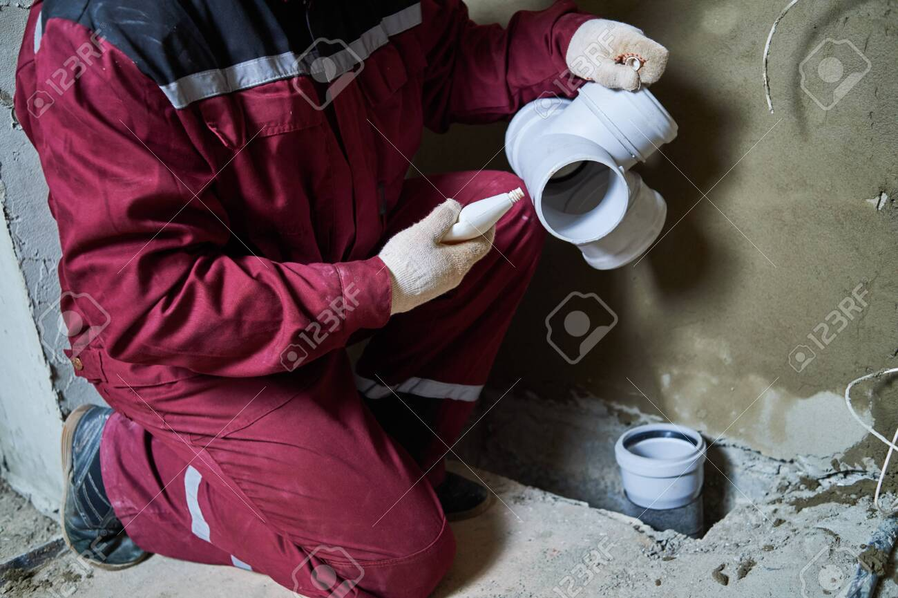 Plumber worker installing sewage pipes in sewerage system - 125560148