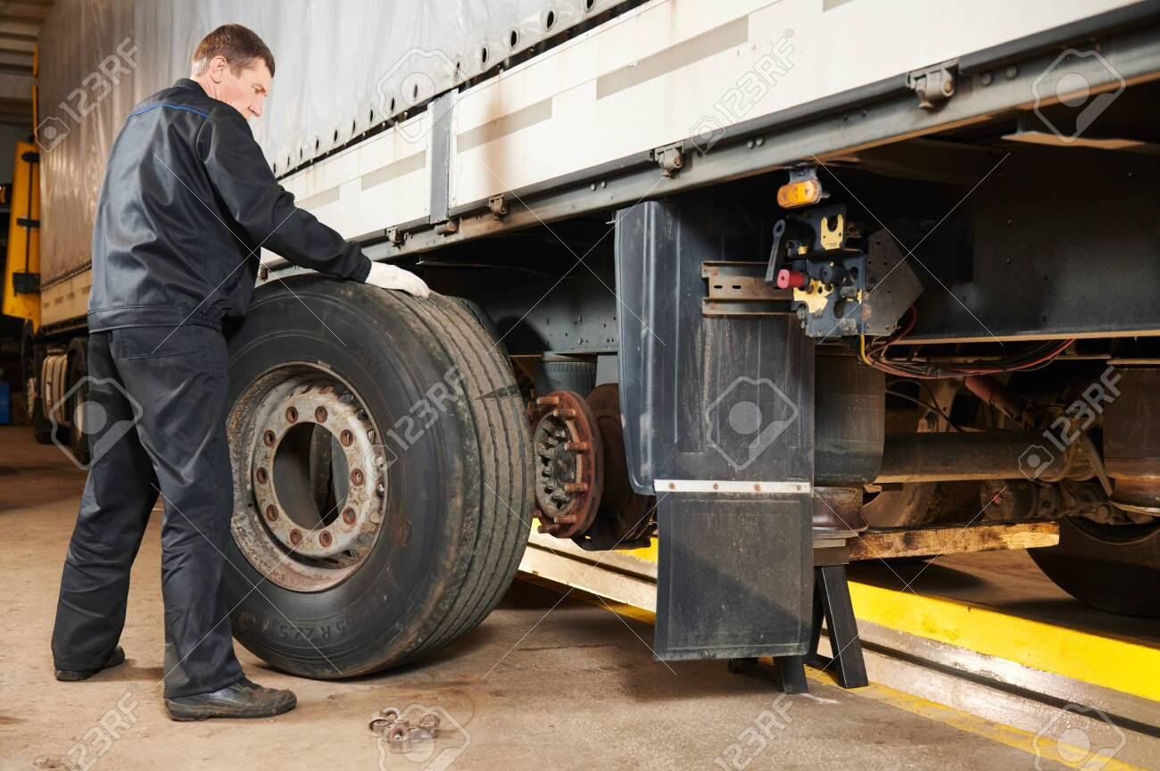 Truck repair service. Mechanic works with tire in truck workshop - 132919579