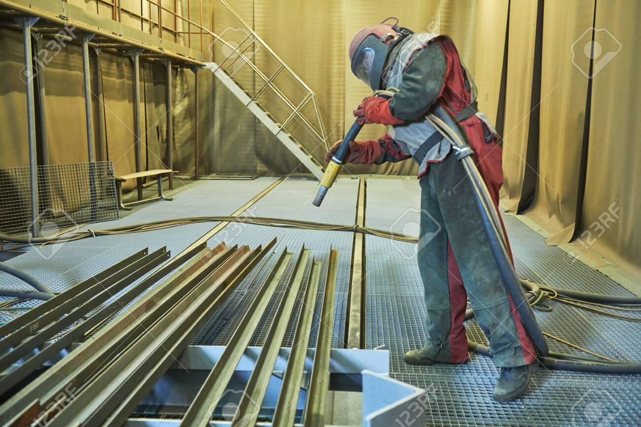 Sandblasting in chamber. Worker makes sand blast cleaning of metal detail - 132919585