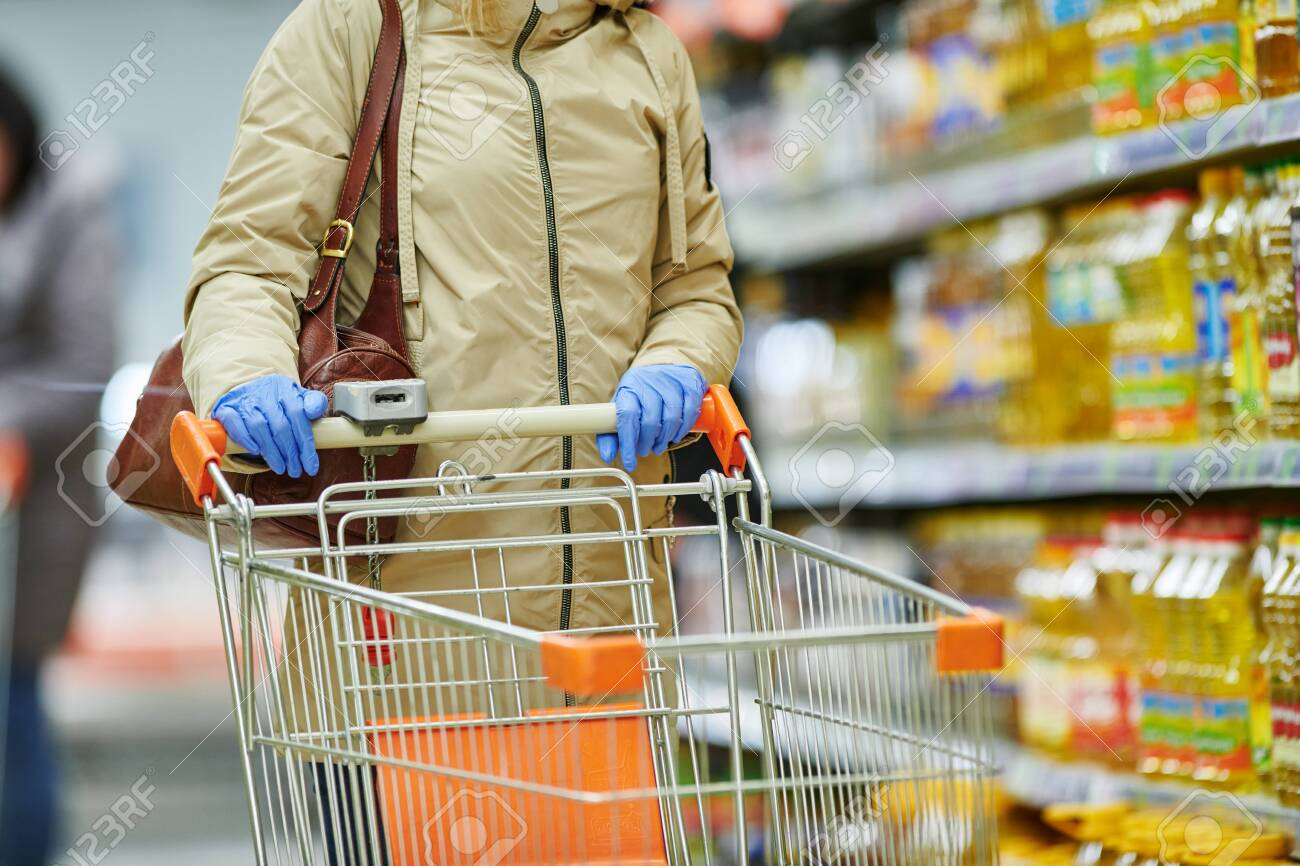 woman shopping at food supermarket in mask and protective gloves at coronavirus covid-19 outbreak - 145126460