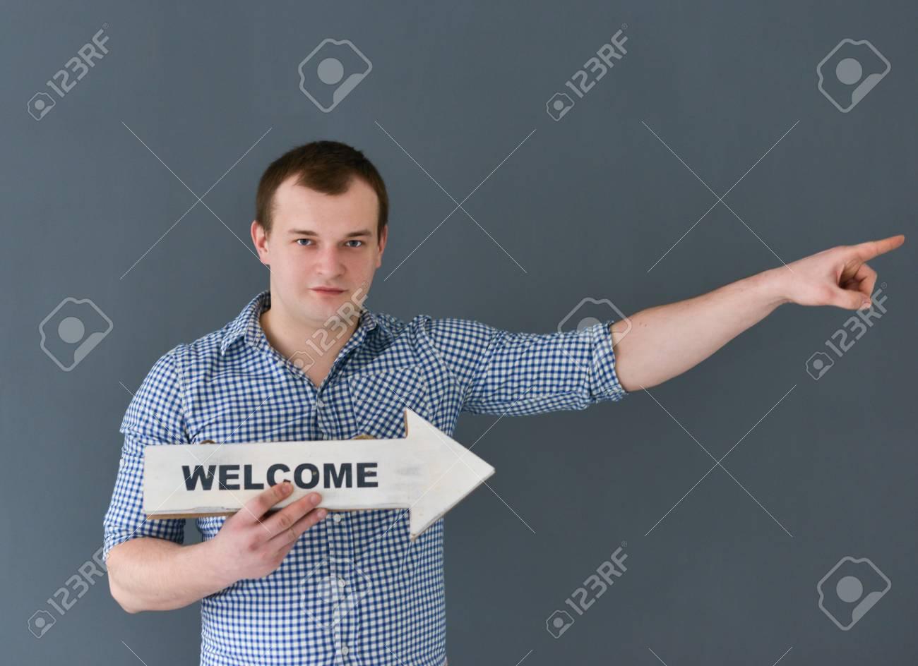 Banque d images - Jeune homme tenant bienvenue conseil bannière permanente 633b79d75b5