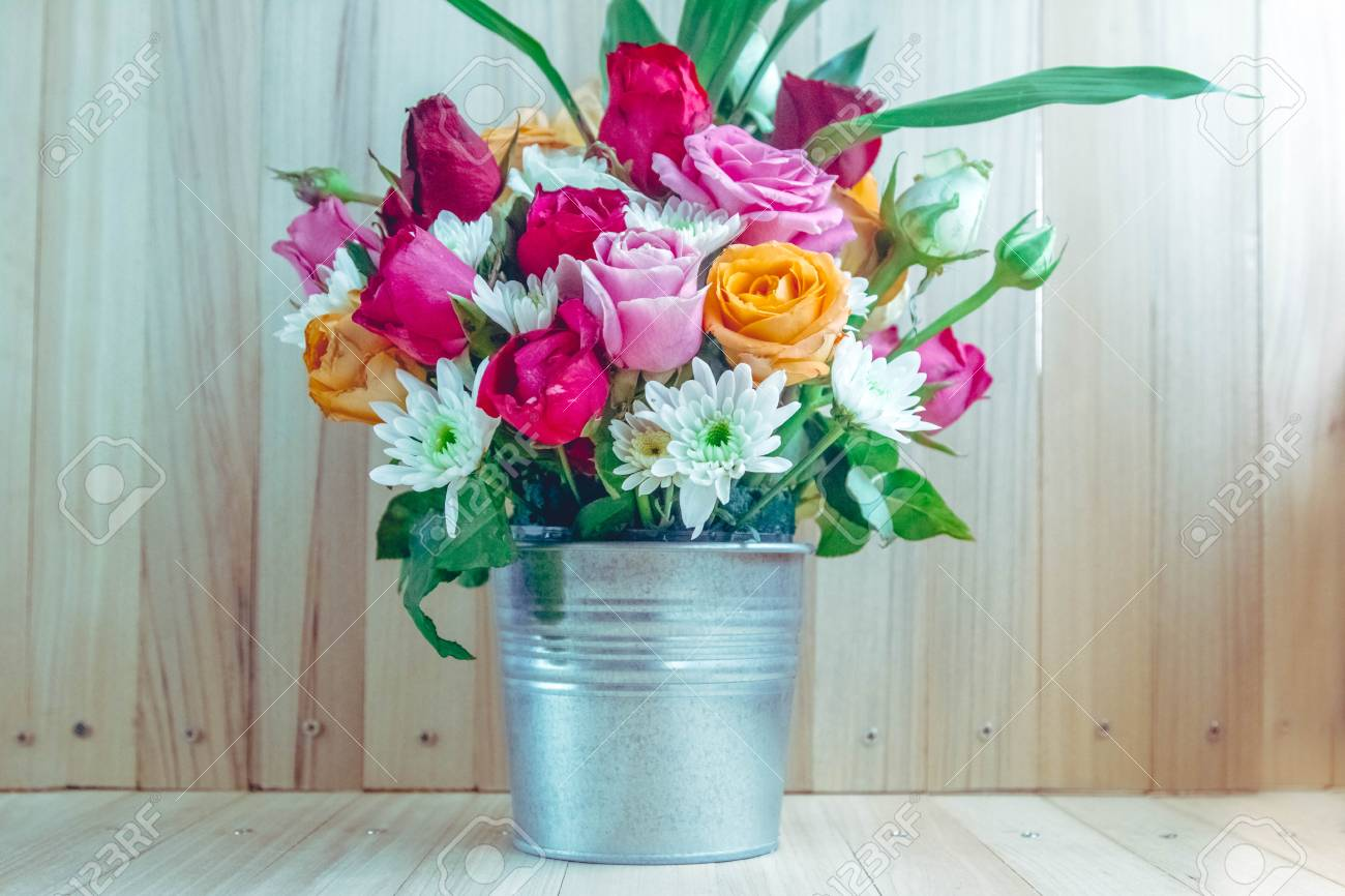 Vase of bouquet roses in aluminium bucket on wooden table set stock photo vase of bouquet roses in aluminium bucket on wooden table set of beautiful flower izmirmasajfo