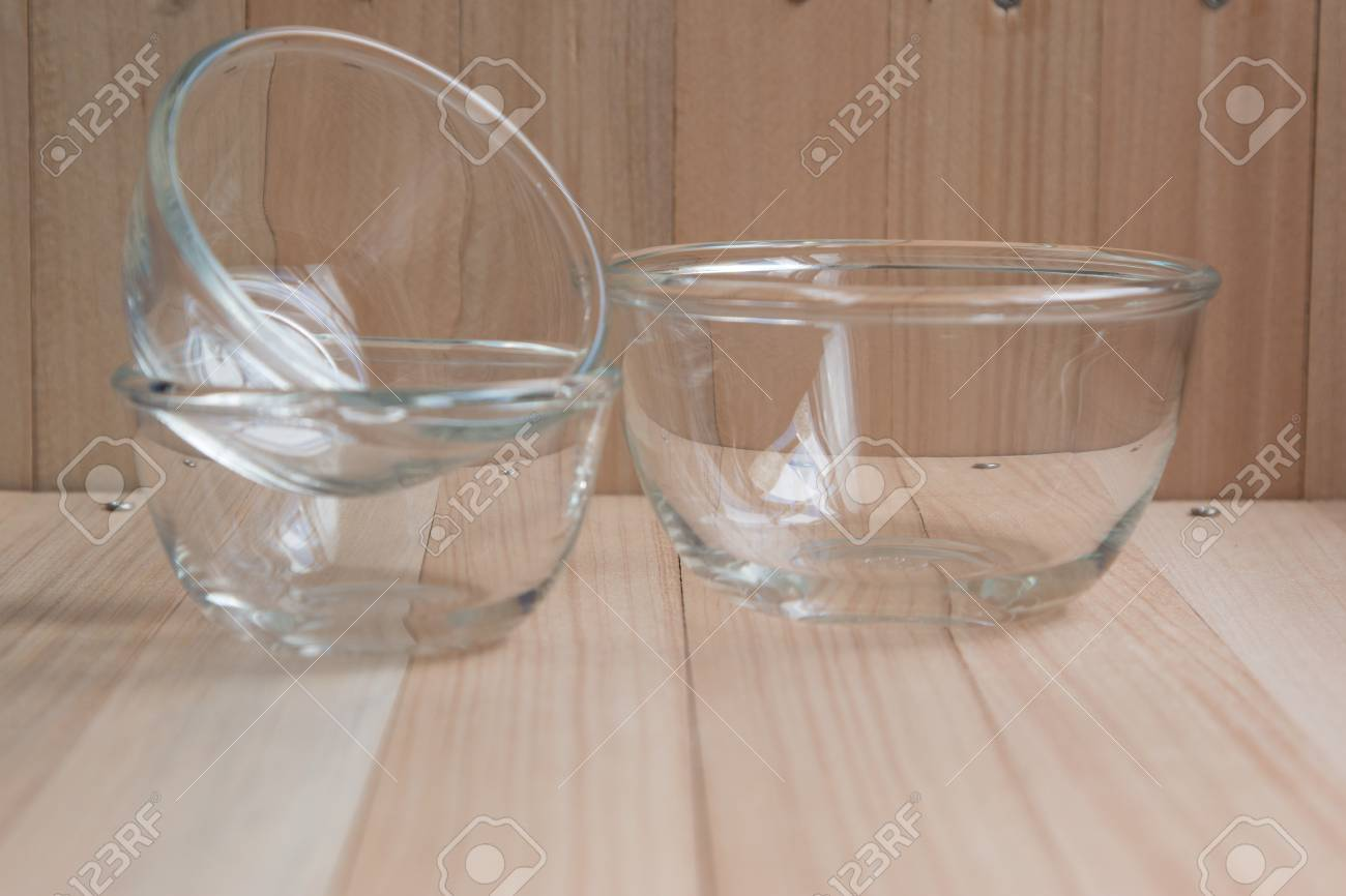 Set of middle and small glass bowl put on the wooden table set of kitchen ware
