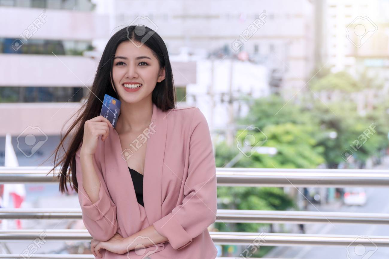 Smiling young woman holding a credit card in city background. Attractive business woman get satisfy and happy with freedom of payment. - 114177099