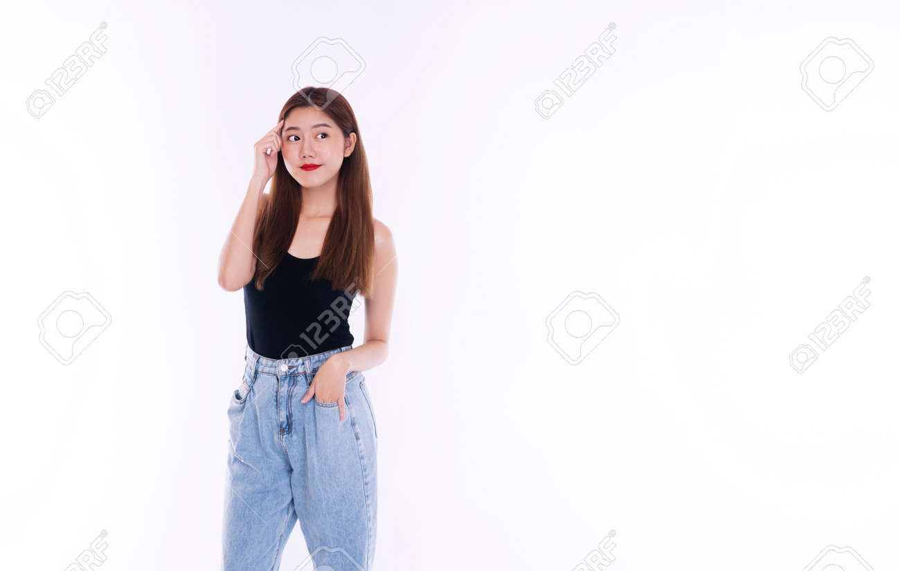 Cheerful smile young women wear t-shirt and jeans holding hand on her head while think good ideas something over isolated white background. Lifestyle concept. - 164159729