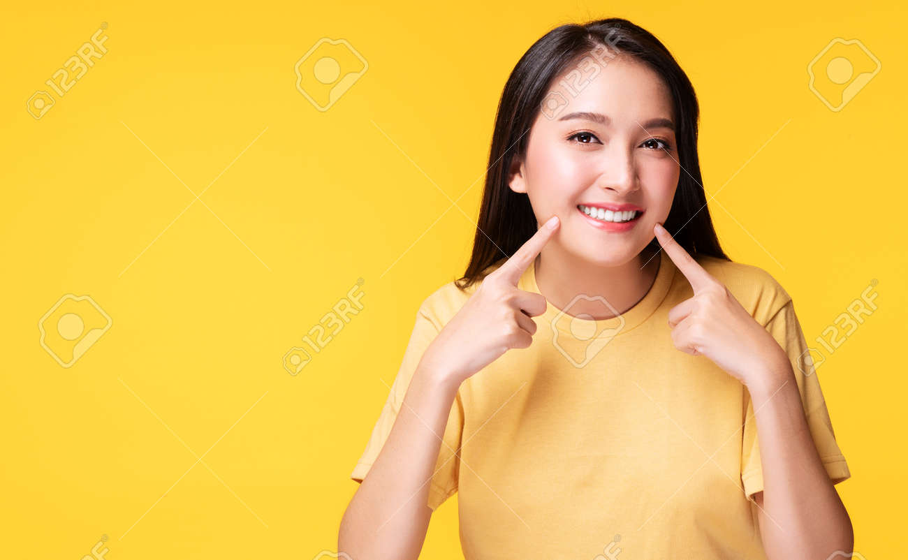 Cheerful young woman using finger point to her whitening teeth while standing over isolated yellow background. She showing her cleaning fresh toothy. Dental care and healthy concept. - 164193901