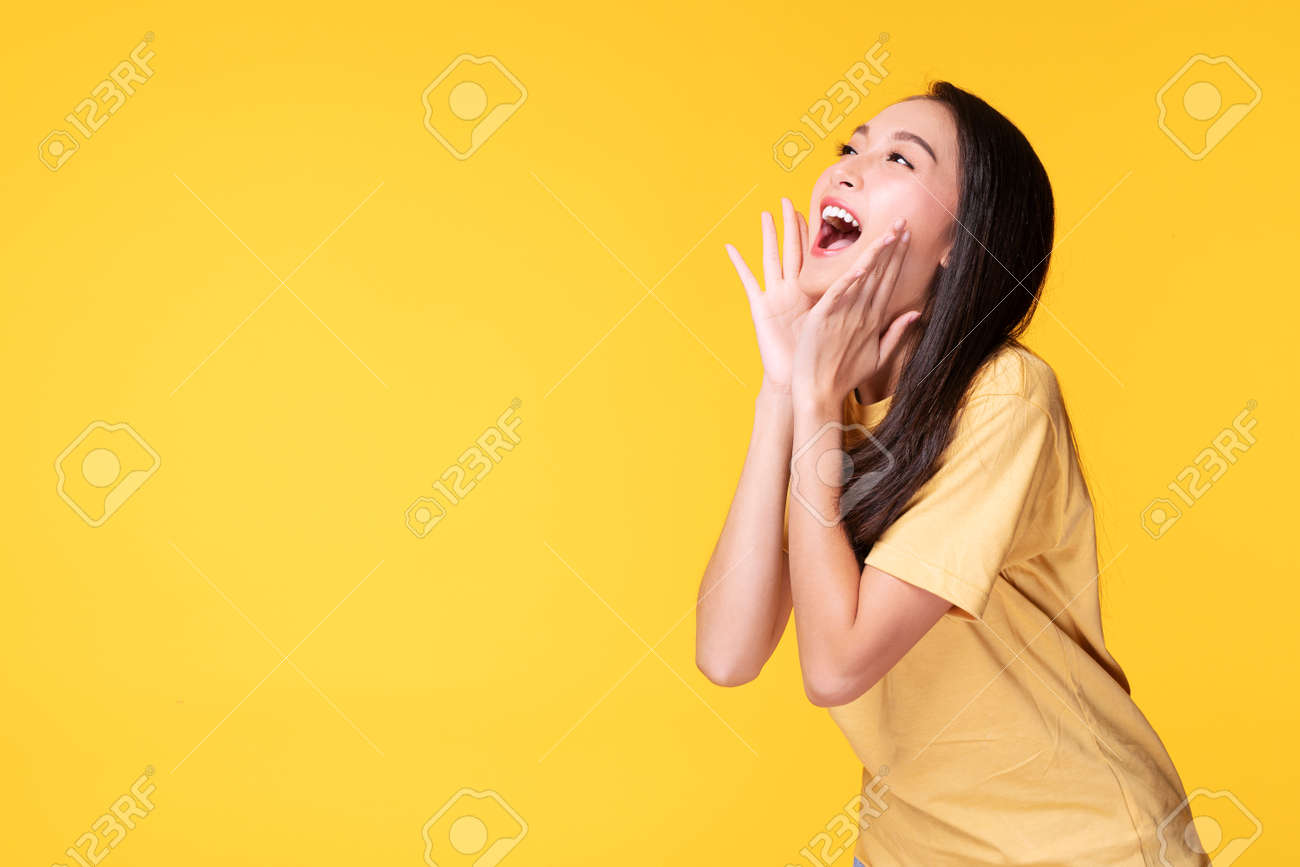 Young woman covers her mouth surprised excited while looking at product on sale promotion or empty copy space over isolated yellow background. - 164193784