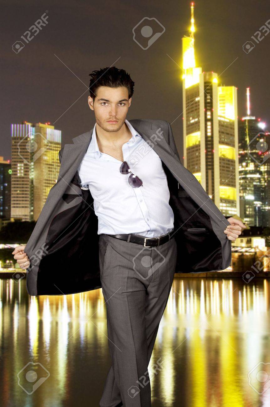 Young Man In A Grey Suit In Front Of A Skyline By Night Stock