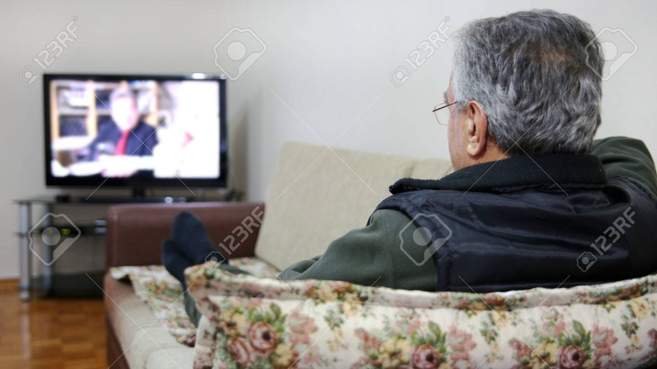 Senior man watching TV show while sitting on sofa in his living room - 23857527