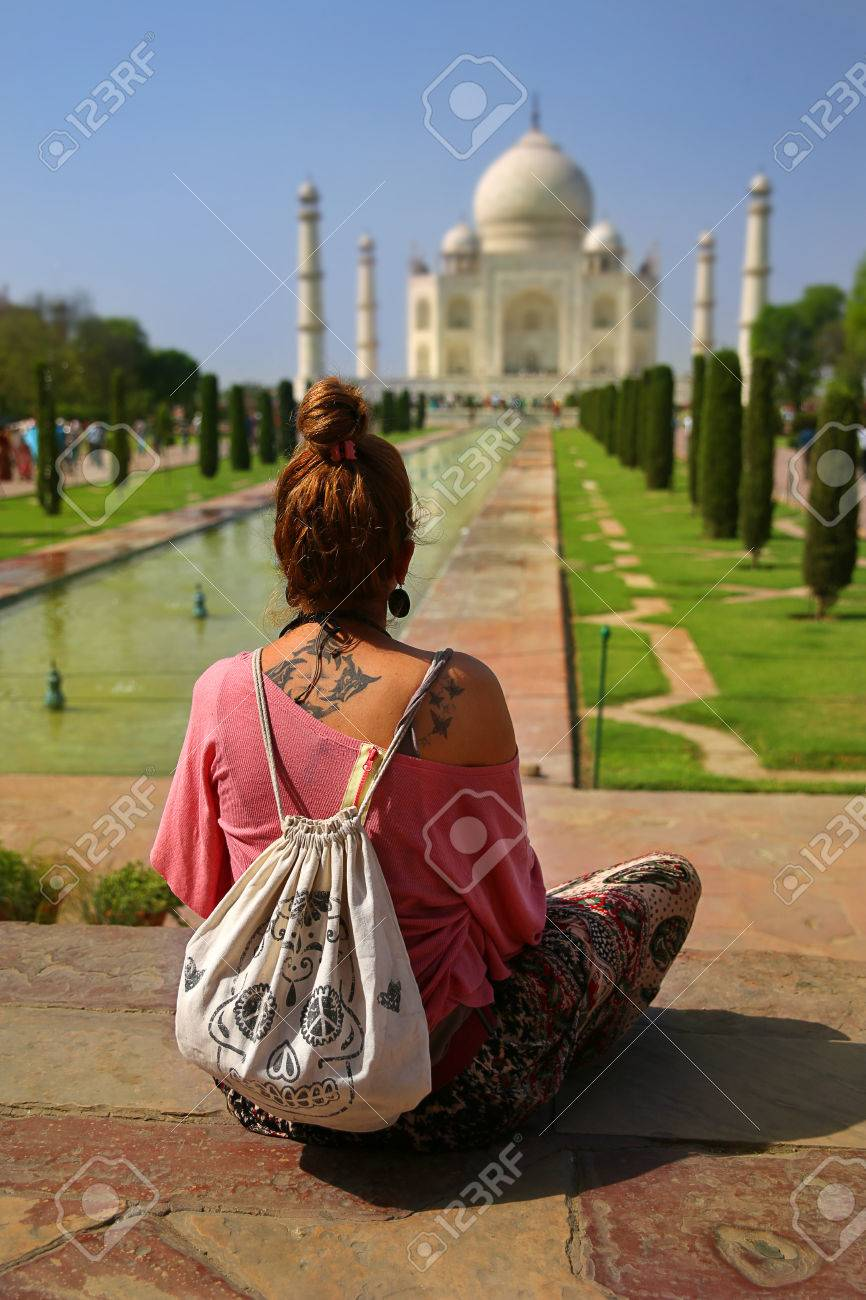 Caucasian woman sitting on bench and looking to Taj Mahal - 23857698