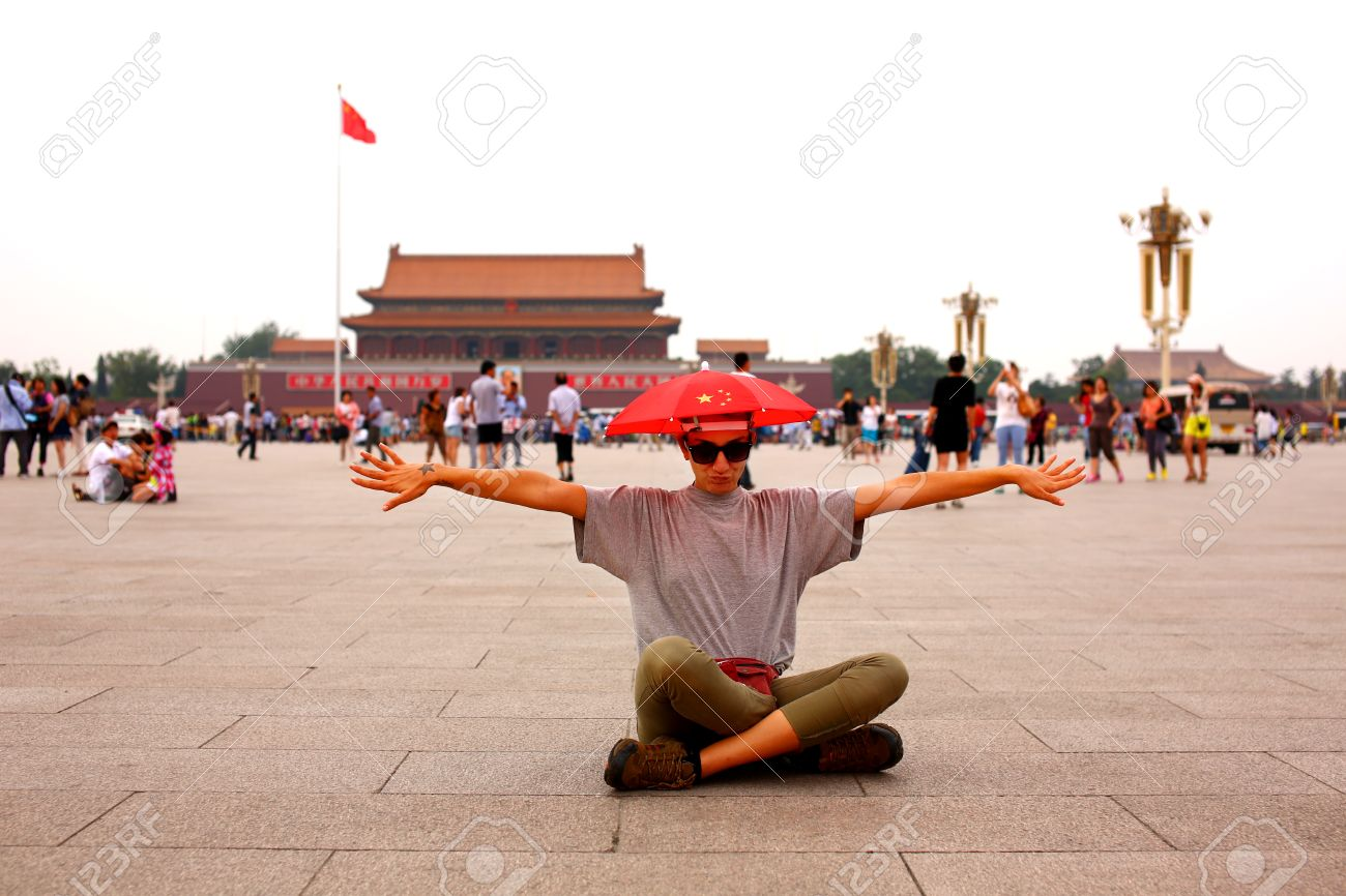 Female tourist wearing hat with chinese flag making funny faces at Beijing, China - 23858239