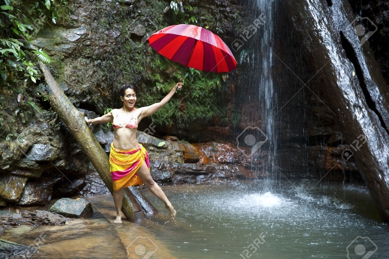 Girl with umbrella at waterfall in borneo rainforest - 24713418