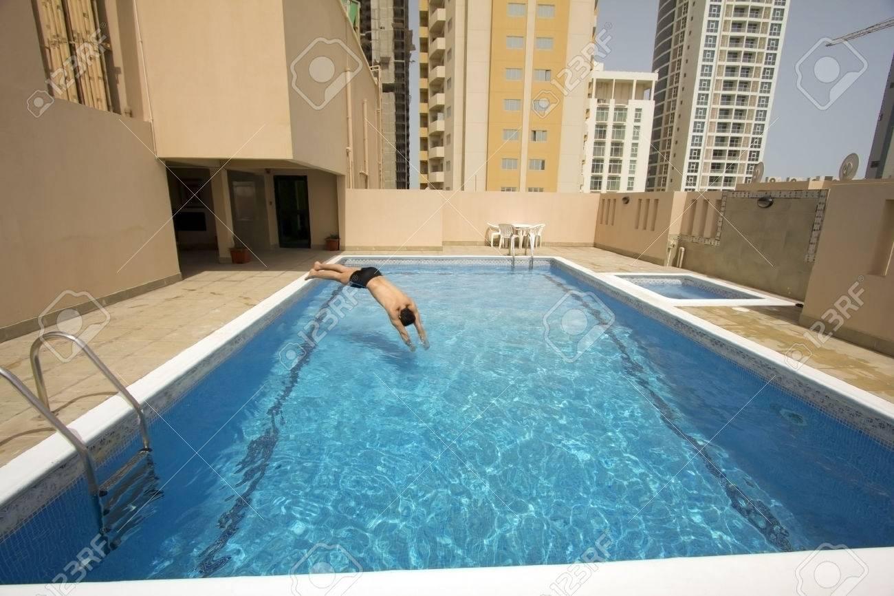 man swim in swimming pool at roof of apartment, bahrain - 25629272