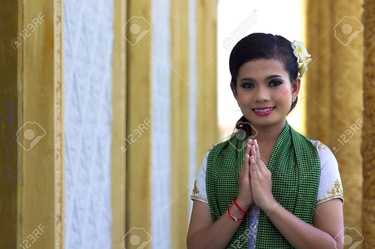 Asian Girl Greets in temple traditional way with both hands - 23857871
