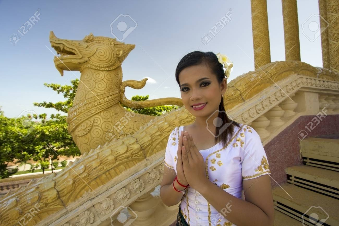 Asian Girl Greets in temple traditional way with both hands - 23857747