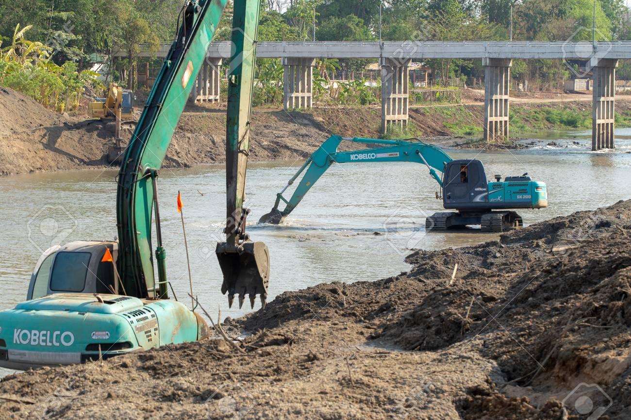 LAMPANG, THAILAND – MAY 3, 2019: Yellow Backhoes digging sand