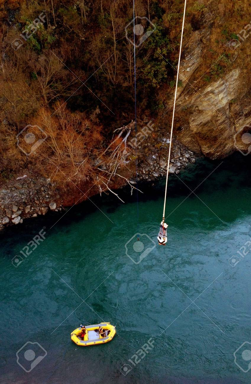 A bungee jumper is waiting to be picked up by the rescue boat
