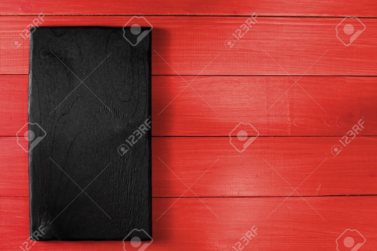 Bureau de cuisson noir sur la table en bois rouge. à plat. vue de