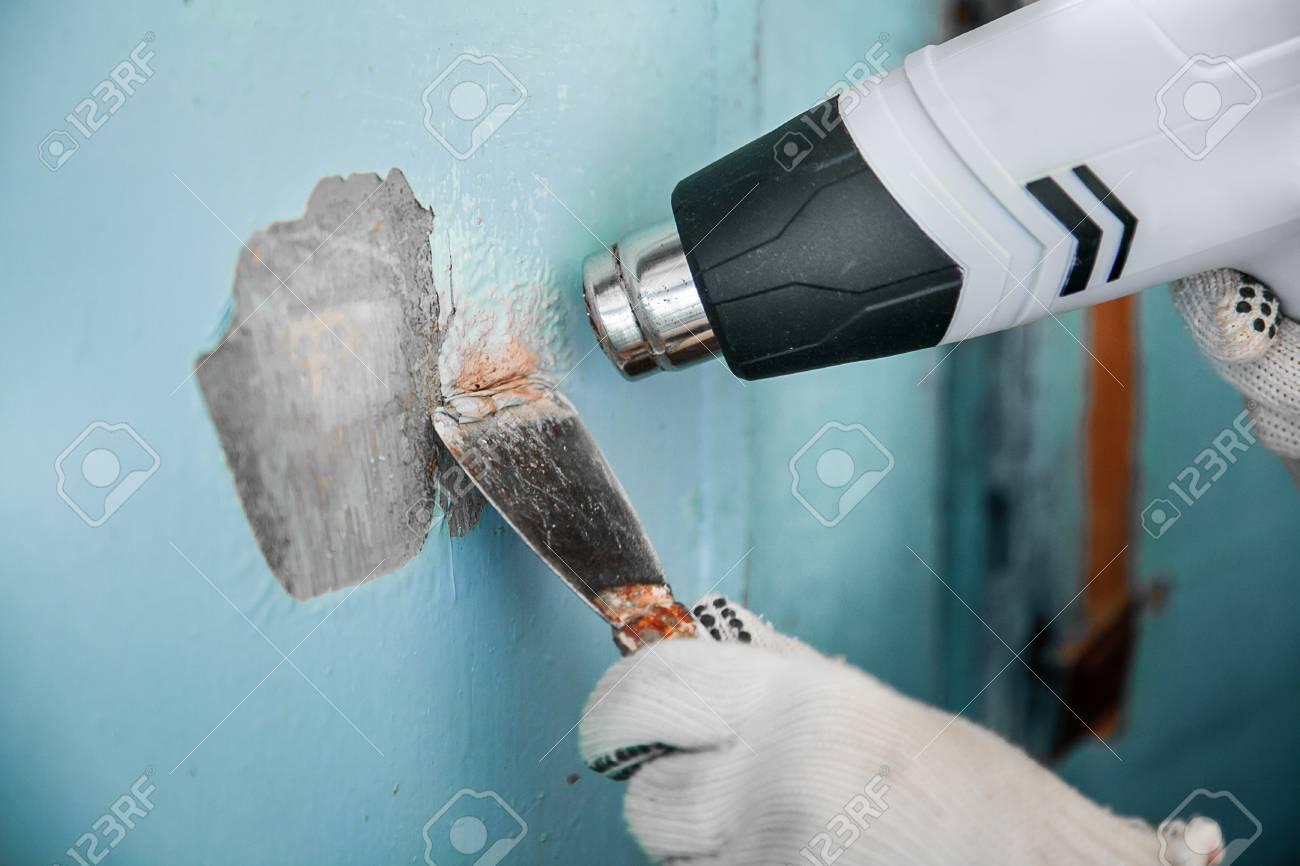 meister entfernt alte farbe aus betonwand mit heißluftfön und