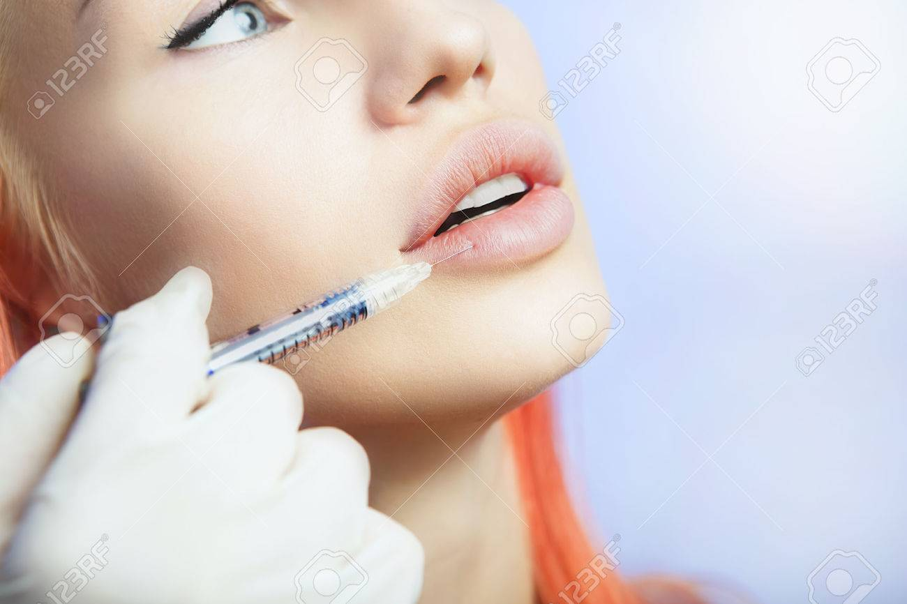 Young Woman Geting an Injection in her Lips in Beauty salon. Beauty Injections -Woman lying in the beautician office. Increase the Lips by Hyaluronic acid, Contouring procedure, revitalization Stock Photo - 48645861