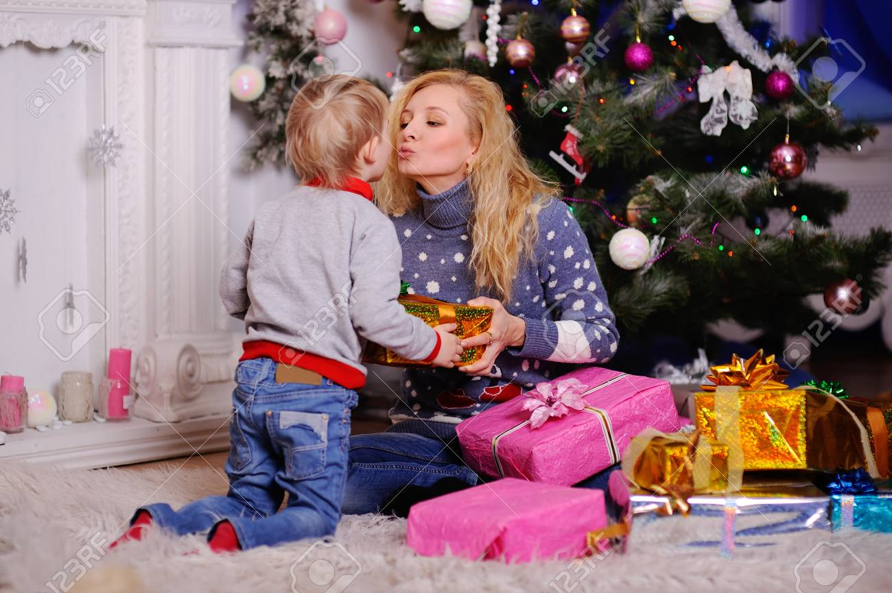 mom gives a small child a christmas gift on the christmas tree background christmas presents