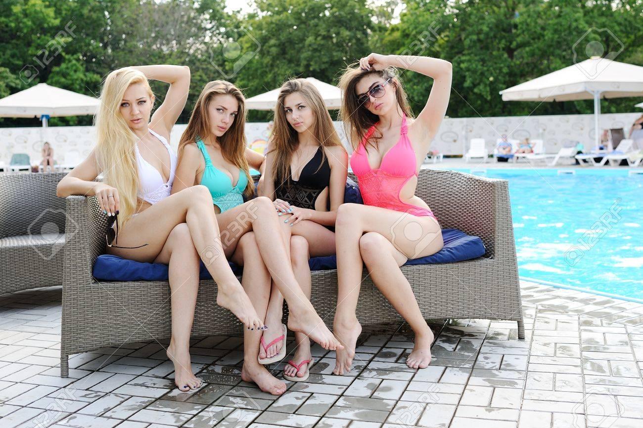 Cuatro Amigas Atractivas En Bikinis Sentado En El Sofá En El Fondo