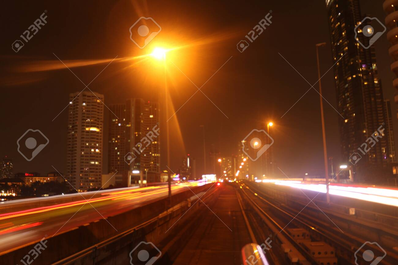 Bangkok City on February 22, 2020 at 11:06 pm: view from the driver's seat from a skytrain on the tracks in front with lightening effects at night with corporate buildings in background - 146066562