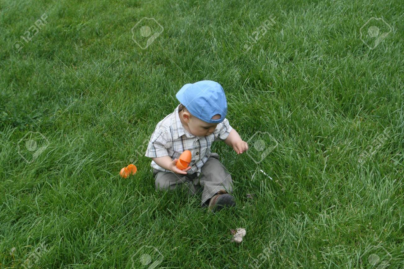 At His First Easter Egg Hunt Finding Orange Plastic Eggs In The Grass Stock