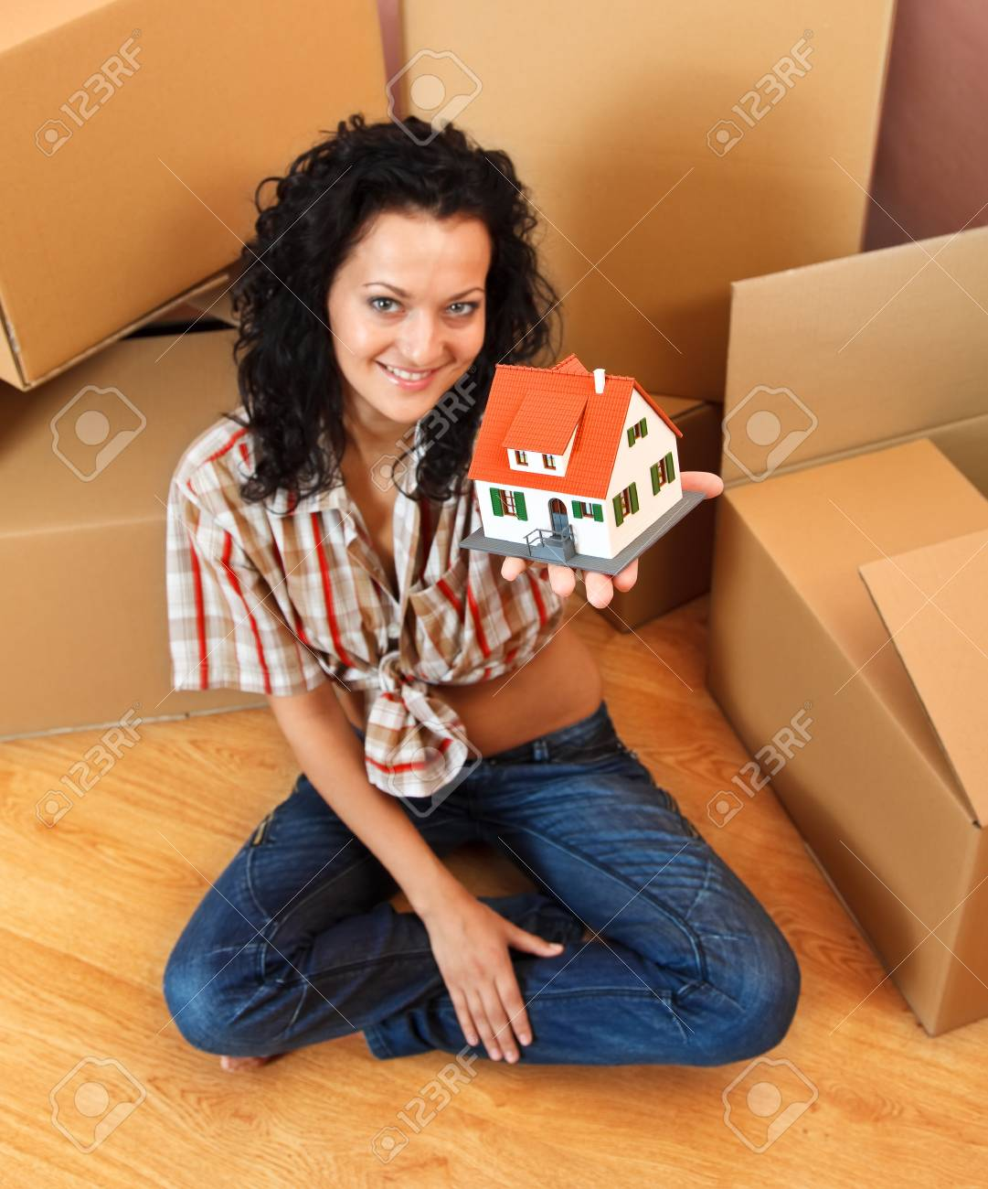 Attractive young woman offering a miniature house, boxes in the background Stock Photo - 9493721