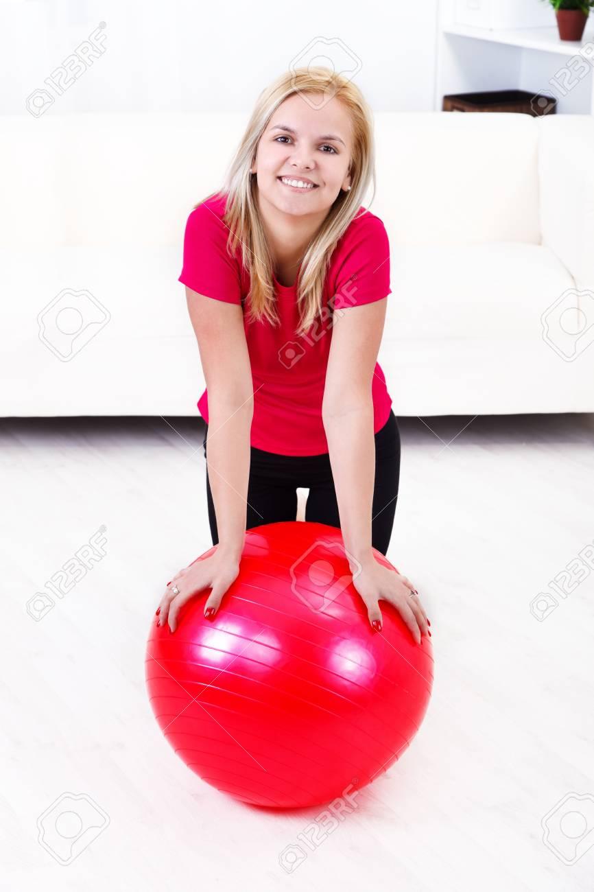 Foto de archivo - Sonriente niña haciendo ejercicios de pilates en casa con  pelota 1add53e3ff99