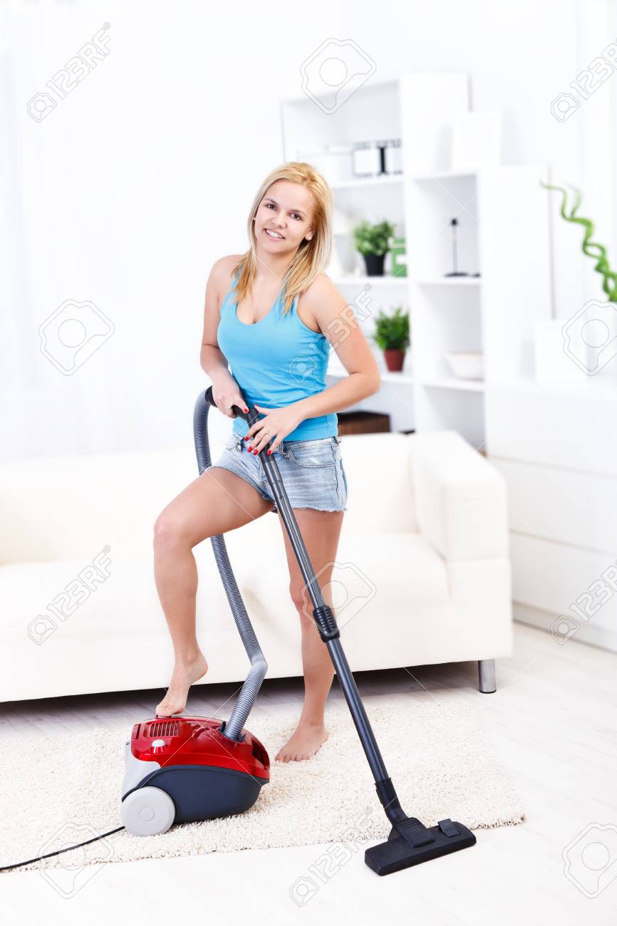Pretty young woman using vacuum cleaner at home Stock Photo - 16890986