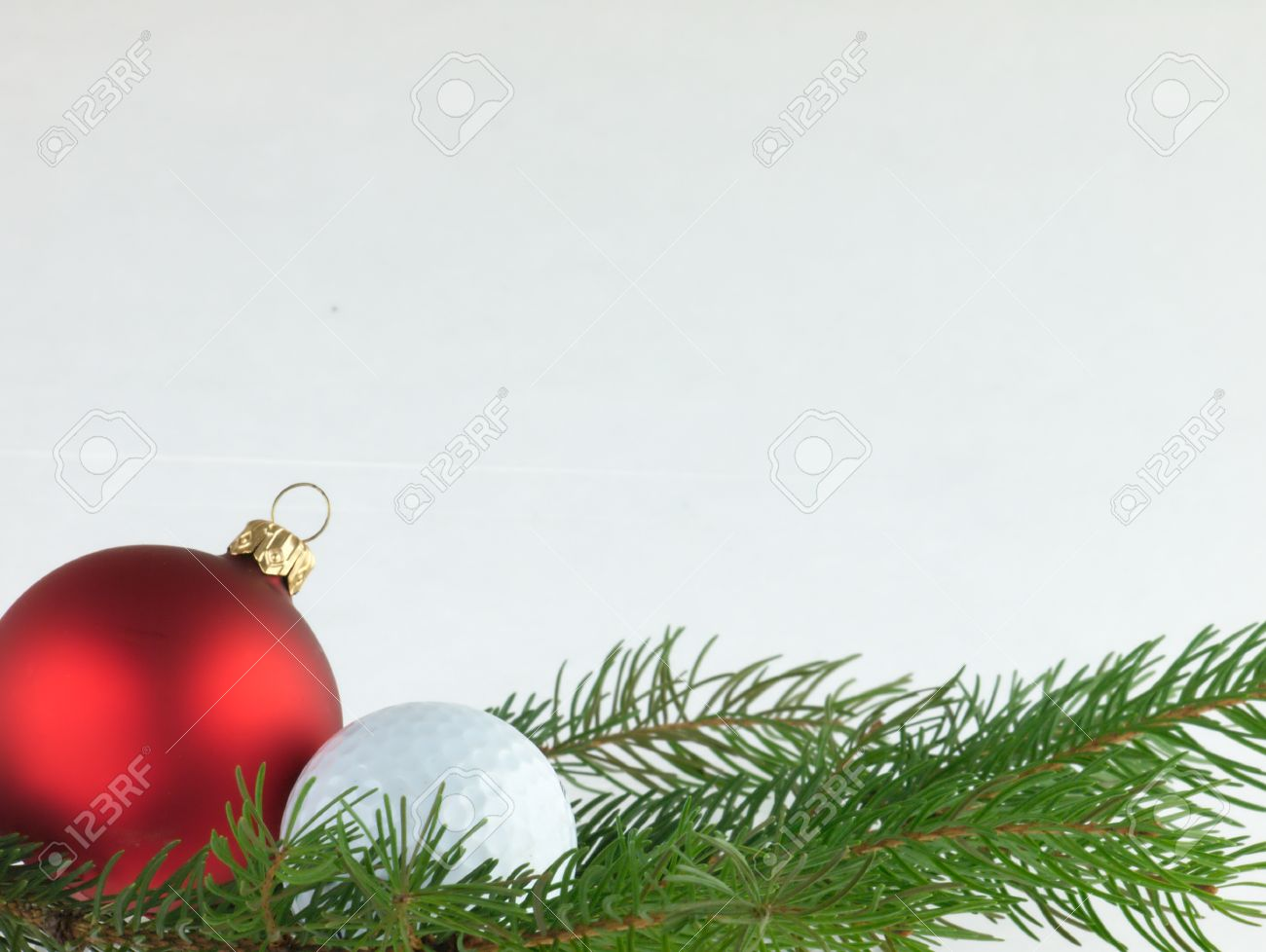 Red Bauble Christmas Tree And Golf Ball With A Sprig Of Pine Trees On Chopping