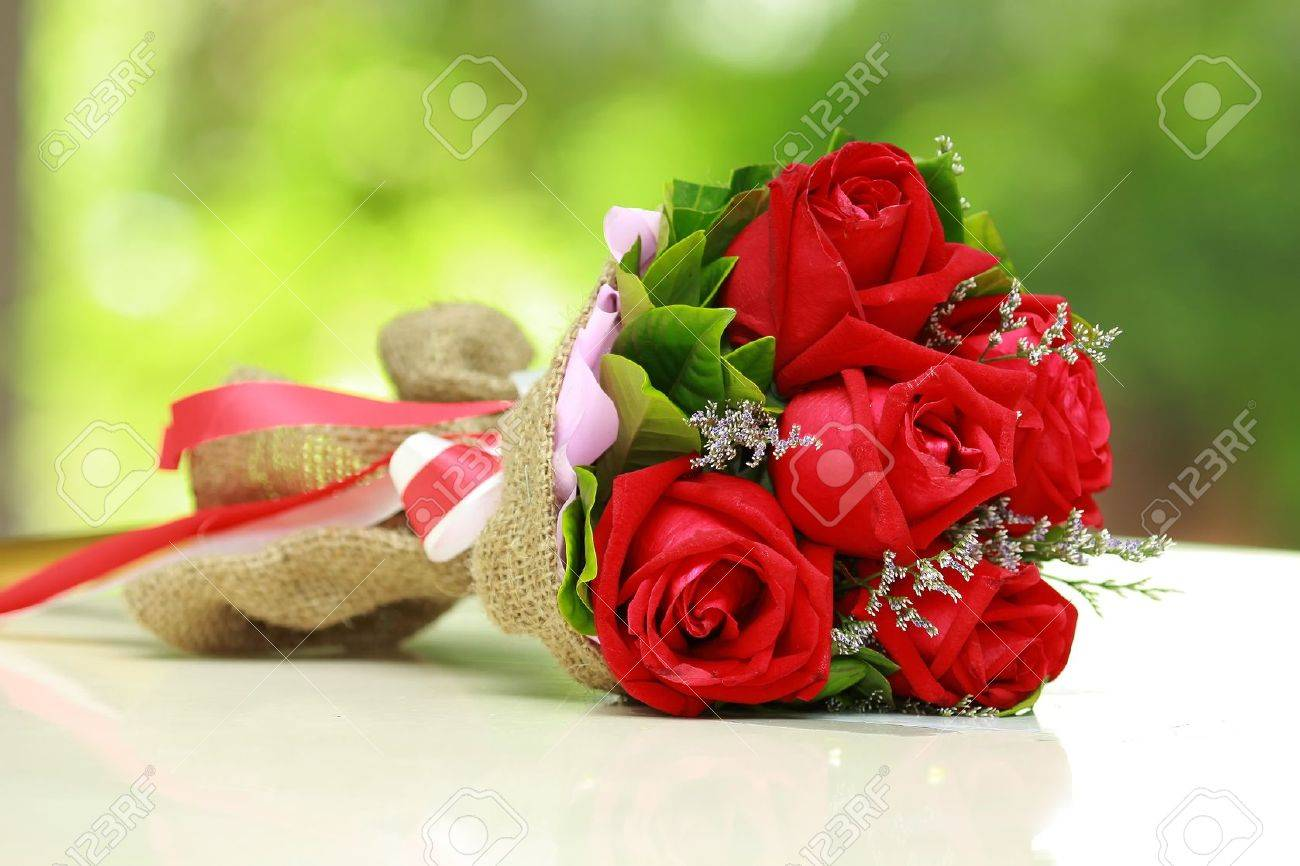beautiful bouquet of bright red flowers, on table on green background - 14447539