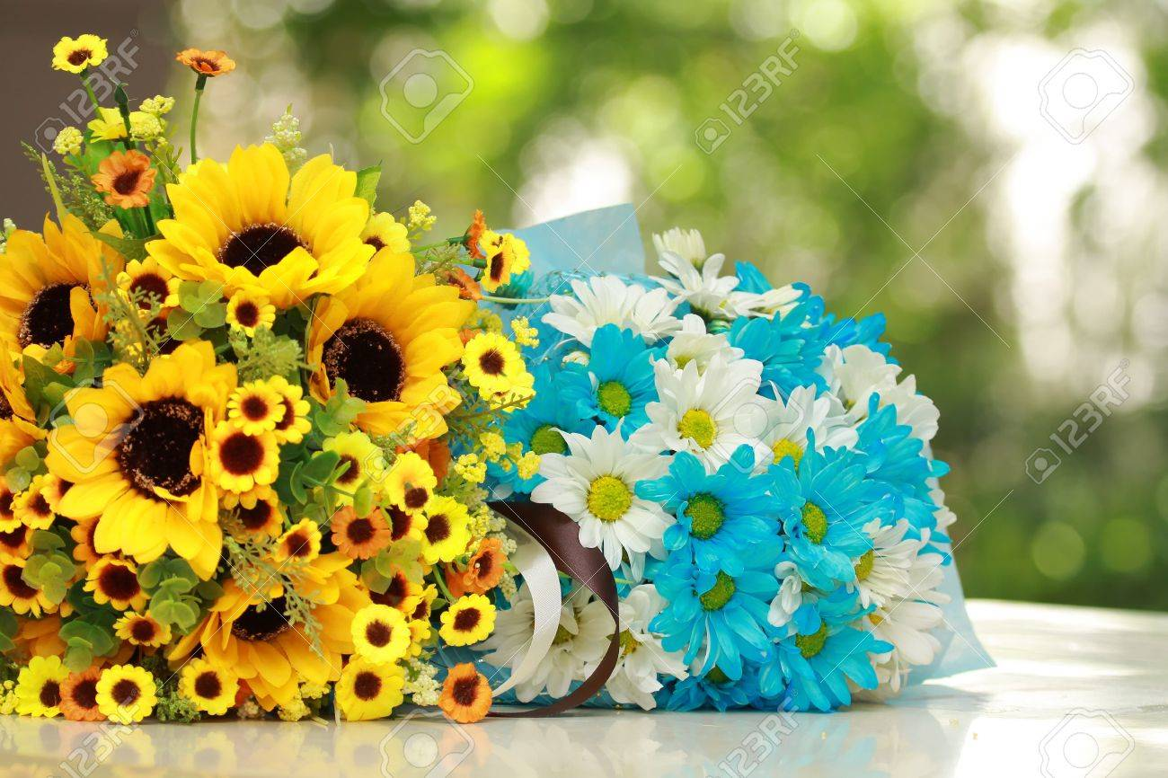 Beautiful bouquet of bright yellow and blue flowers on table beautiful bouquet of bright yellow and blue flowers on table on green background stock photo izmirmasajfo Image collections