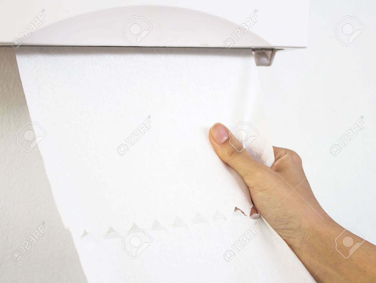 Disposable bathroom hand towels - Hand Woman Pull Tissues Paper Towel Dispenser On The Wall In The Bathroom Stock Photo