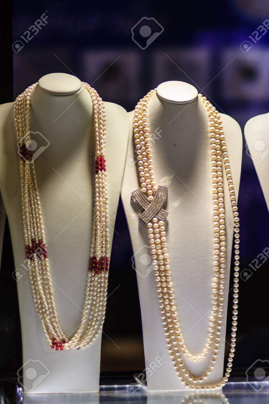 5da4c8311848 Beautiful long pearl necklaces are displayed at a jewelry shop. Poor light  with noise grain