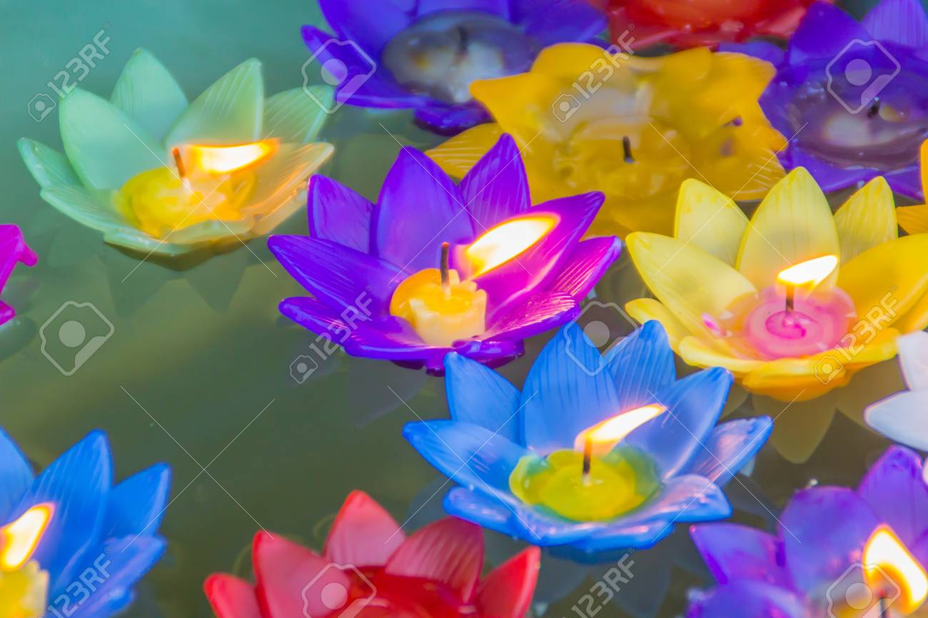 Colorful Lotus Flower With Burning Candles Are Floating On The