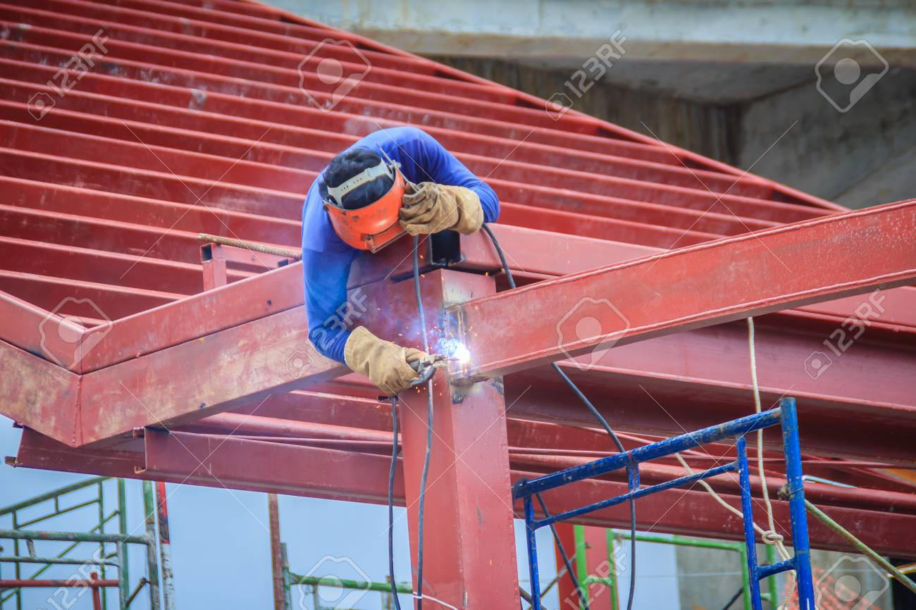 Risky welder while climbing and welding on top of the steel roof structure work at the building construction site. Skilled worker is welding on the high steel structure at the construction project. - 112996752