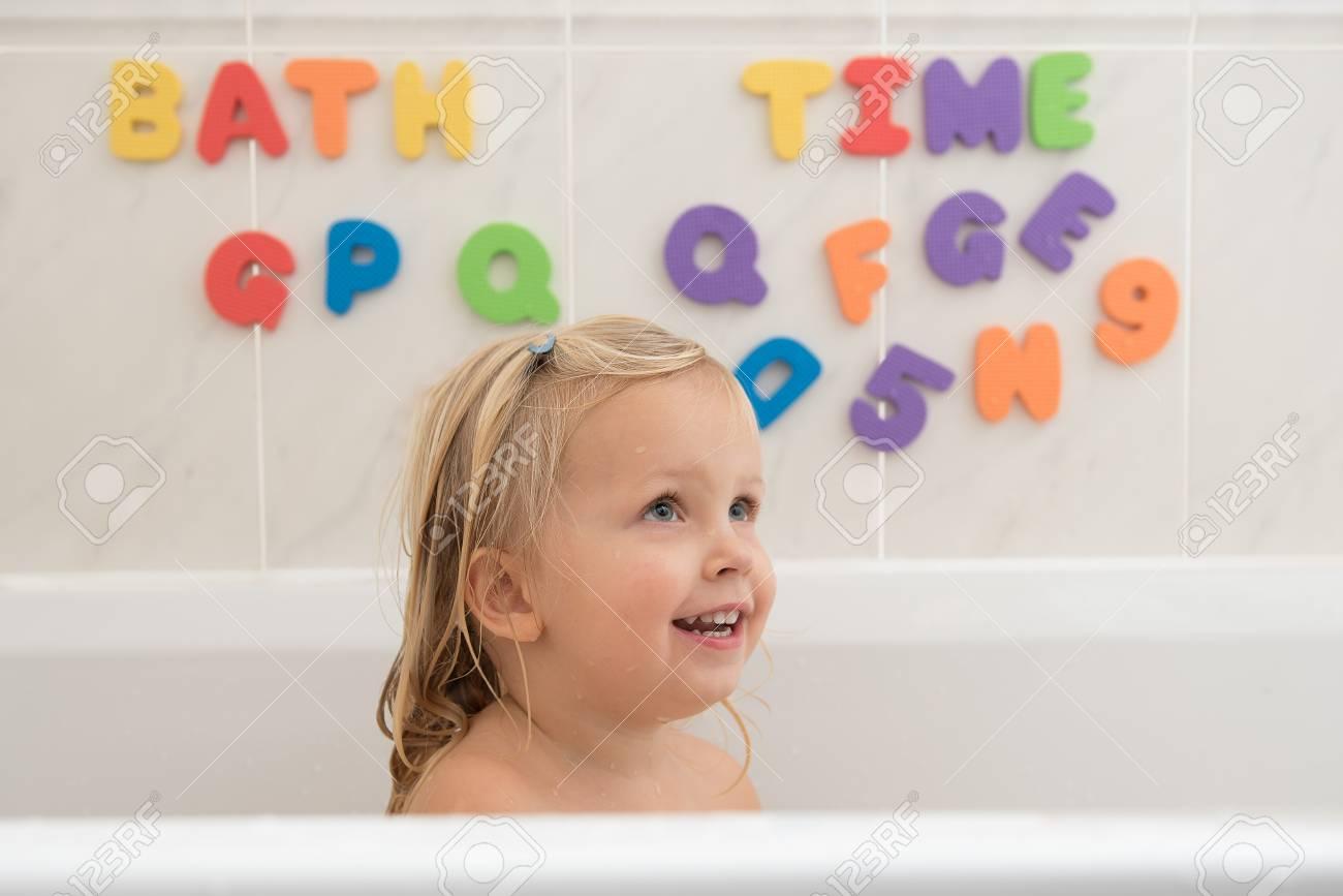 Lächelndes Kleines Mädchen Im Badezimmer Mit Bunten Schaumgummizeichen Und  Zahlen Im Hintergrund. Wasserspaß Für Kinder
