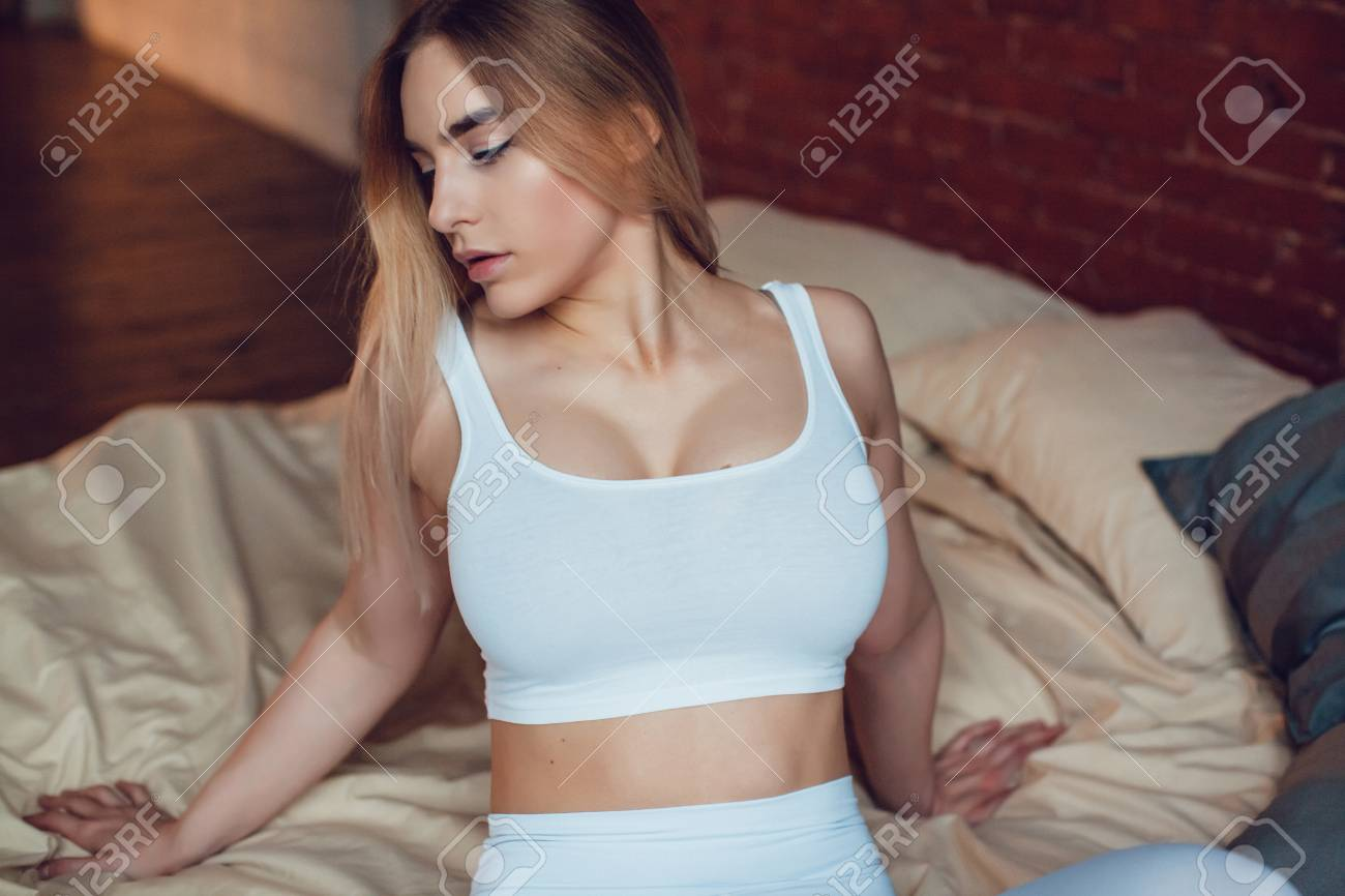 Superb Sexy Blonde Woman With Huge Breast In A White Tank Top Sitting Evergreenethics Interior Chair Design Evergreenethicsorg