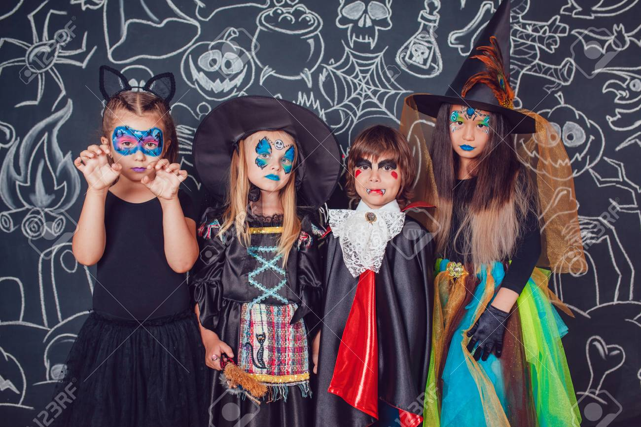 children in scary halloween costumes stand against a wall with
