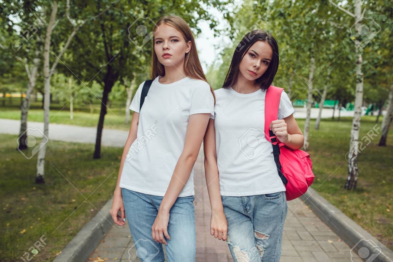 Girls in white T-shirts walking in the park. Mock up. - 86521116