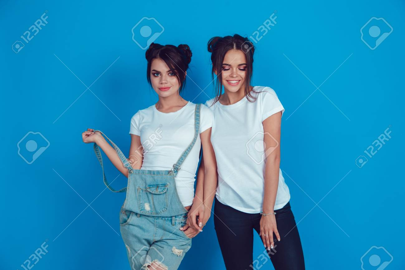 Attractive women in a white t-shirts stands on a blue background. Mock-up. - 94434596