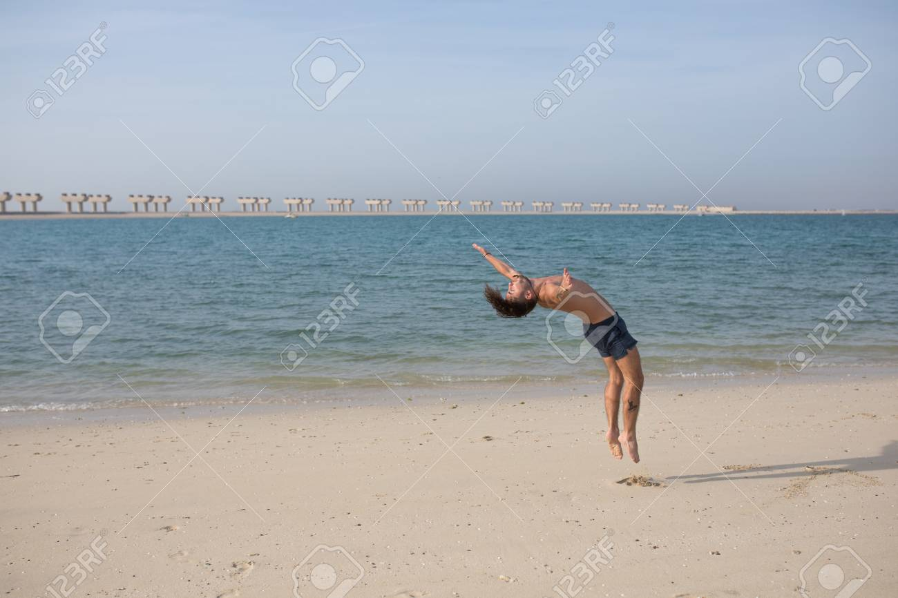 bc9567724b8db5 Young man doing somersault on the beach. Stock Photo - 96753040