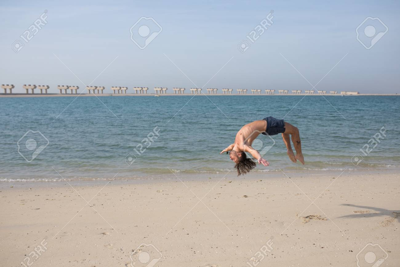 ed17124d4a0ad1 Young man doing somersault on the beach. Stock Photo - 96753041