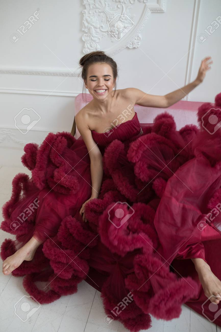 Cheerful Young Woman In A Burgundy Ball Gown. Stock Photo, Picture ...