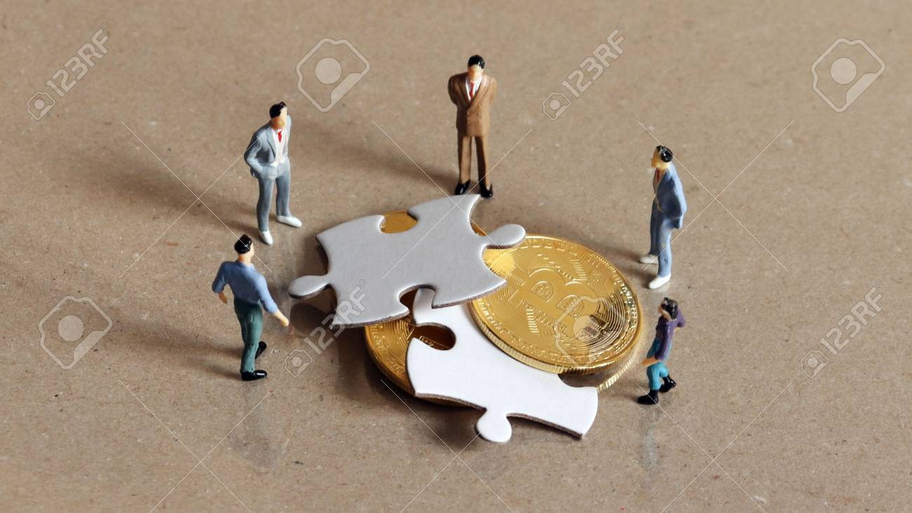 Five miniature people staring down two pieces of the puzzle and bitcoin. - 96170255