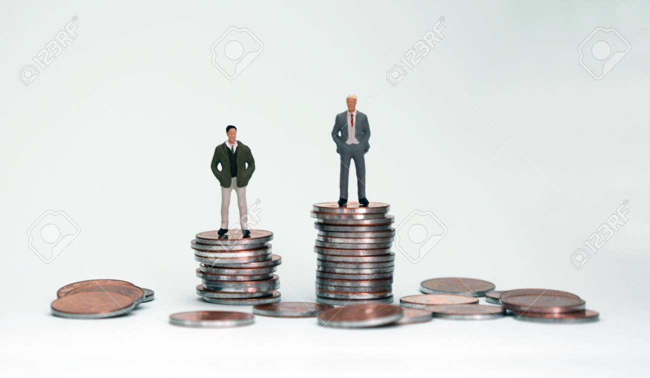 Two miniature men on top of another pile of coins. - 97355690
