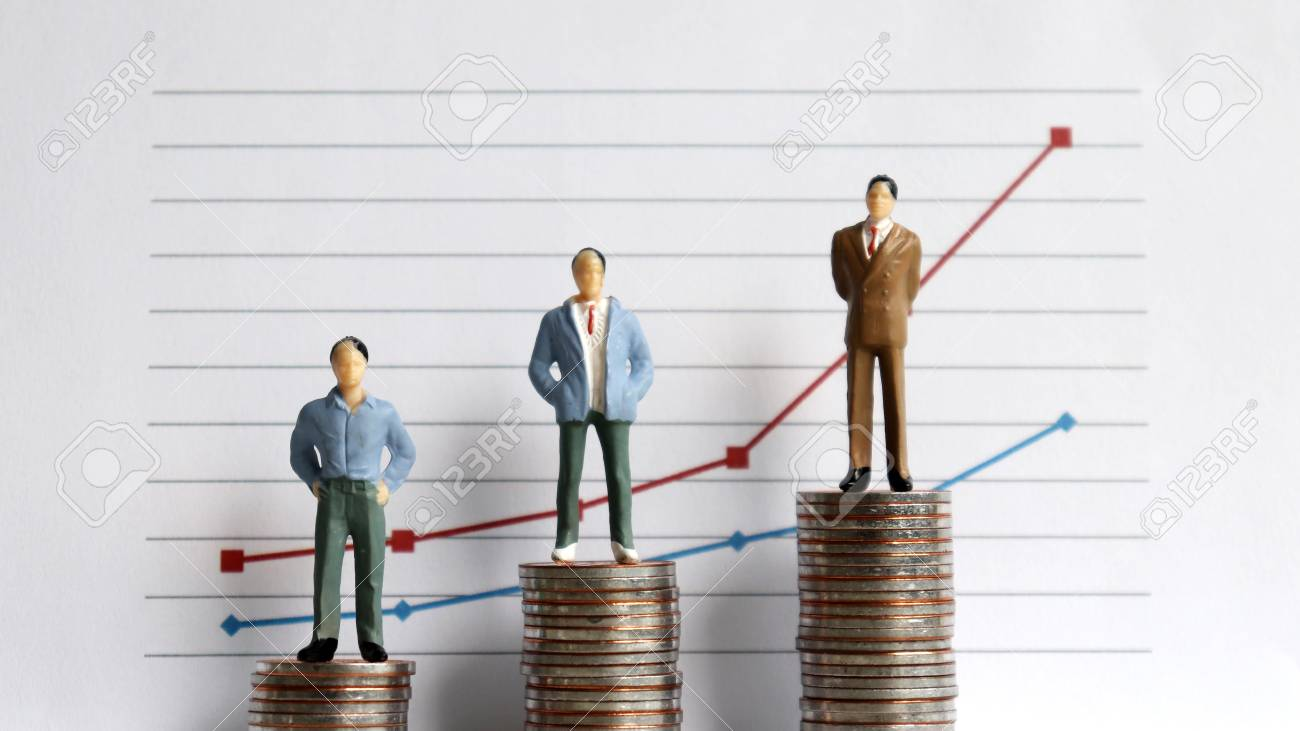 Miniature people standing on a pile of coins in front of a graph. The concept of the difference between occupation and income. - 99966188